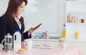18123690 - young business woman text messaging while having breakfast in the kitchen